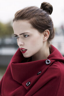 Portrait of young woman with red lips wearing red cape - GD000483