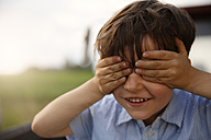Portrait of smiling little boy covering eyes with his hands - FKIF000061