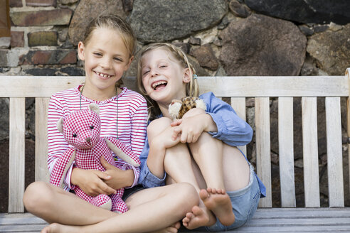 Portrait of two happy girls sitting on a bench with their soft toys - FKIF000038