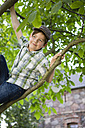 Portrait of little boy climbing in a tree - FKIF000043
