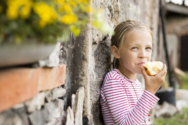 Portrait of smiling little girl eating an apple - FKIF000047