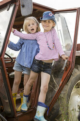 Portrait of two smiling little girls standing on a tractor - FKIF000076