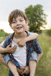 Portrait of smiling little boy giving his brother piggy back - FKIF000052