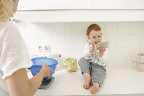 Little girl sitting on kitchen counter with smartphone - FSF000249