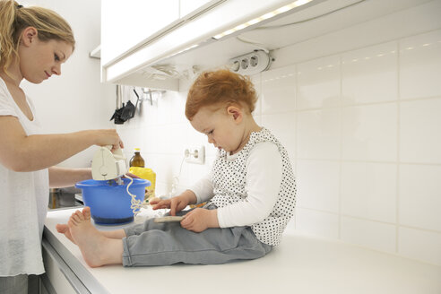 Little girl sitting on kitchen counter with smartphone while her mother baking - FSF000240