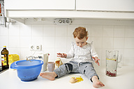 Little girl sitting on kitchen counter looking at broken egg - FSF000206