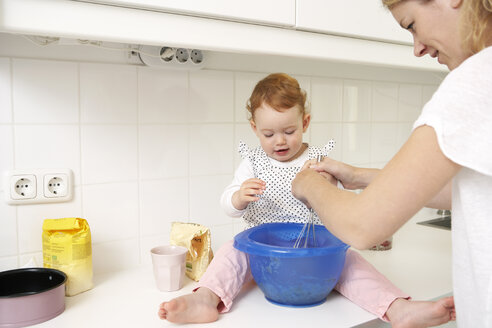 Mother and little daughter baking cake together in their kitchen - FSF000211