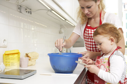 Mother and little daughter baking cake together in their kitchen - FSF000251