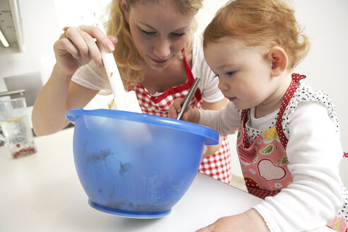 Mother and little daughter baking cake together in their kitchen - FSF000243