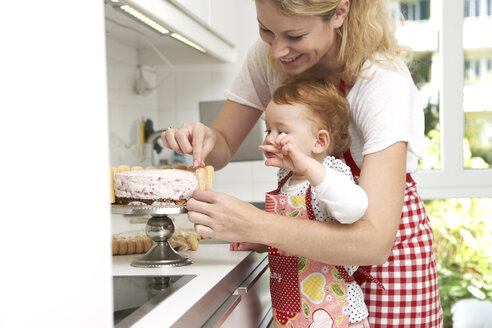 Mother and little daughter baking cake together in their kitchen - FSF000221