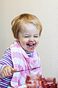 Portrait of laughing little girl covered with red jam - JFEF000505