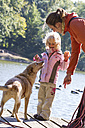 Mother and daughter and their begging dog standing on a boardwalk - JFEF000514