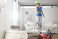 Boy in living room tangled in vacuum cleaner - FSF000272