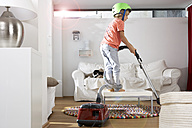 Boy in living room hoovering - FSF000275