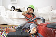 Exhausted boy in living room with cat and vacuum cleaner - FSF000279