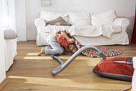 Boy in living room hoovering under carpet - FSF000257