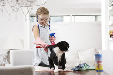 Girl with diving goggles cleaning cat on dining table - FSF000285