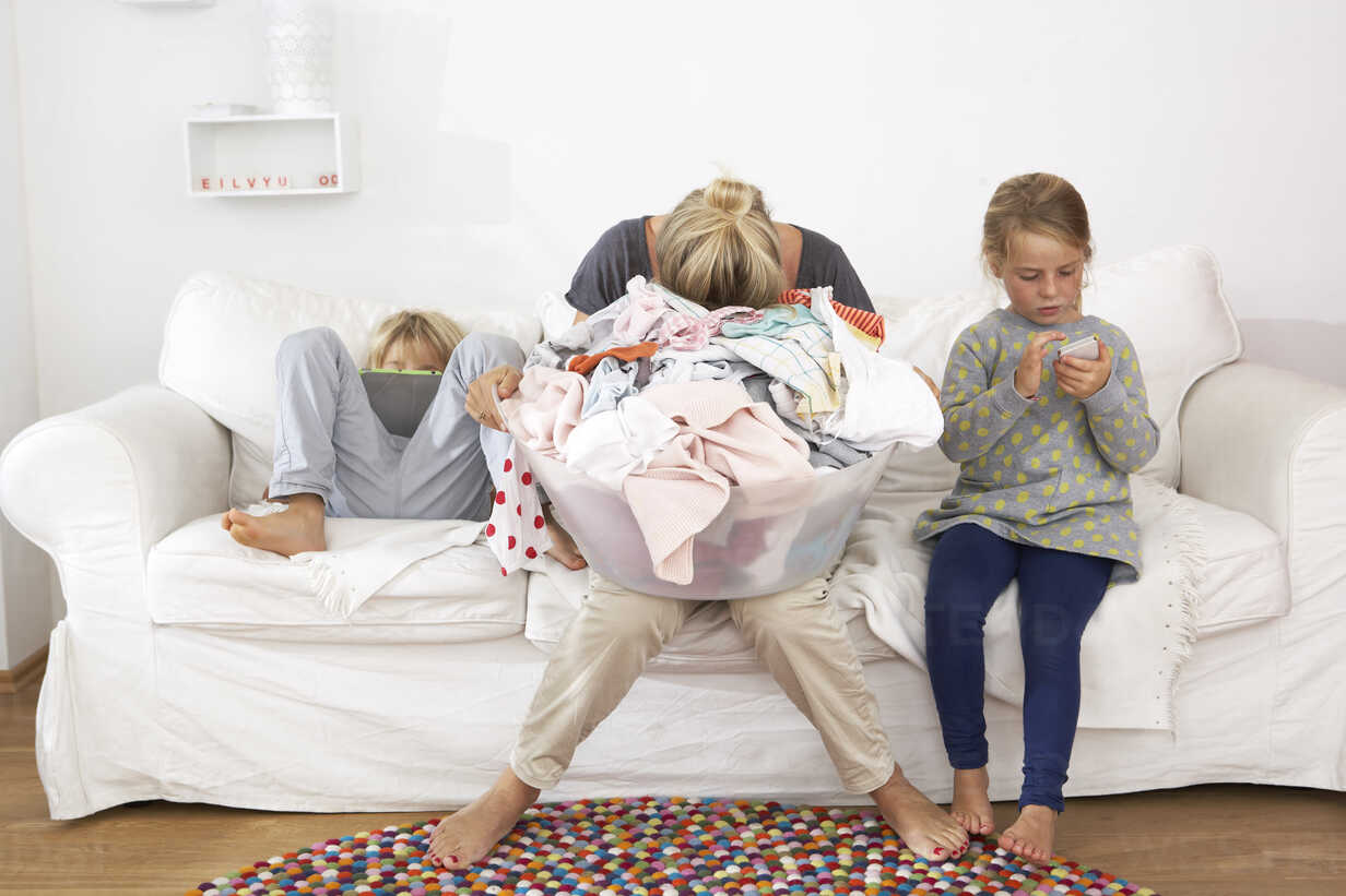 Exhausted mother with laundry basket on couch with children using digital tablet and cell phone - FSF000261 - Sandra Bielmeier/Westend61