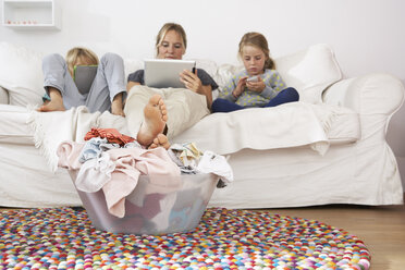 Mother, daughter and son on couch using digital tablet and cell phone with laundry basket on floor - FSF000262