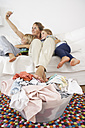 Mother, daughter and son on couch taking a selfie with laundry basket on floor - FSF000265