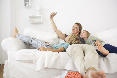 Mother, daughter and son on couch taking a selfie - FSF000268