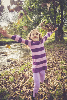 Little girl throwing autumn leaves - SARF000931