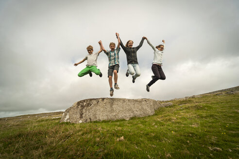 United Kingdom, England, Cornwall, Children jumping from stone - PAF001023