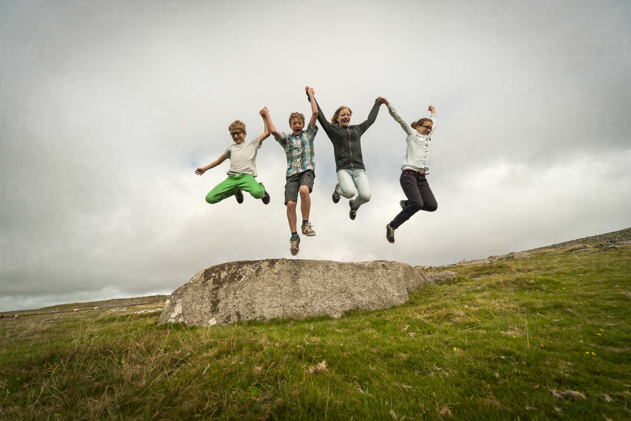 United Kingdom, England, Cornwall, Children jumping from stone - PAF001023 - Andreas Pacek/Westend61