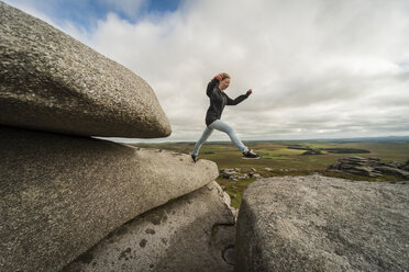 United Kingdom, England, Cornwall, Bodmin Moor, Rough Tor, Rock formation, Girl jumping - PAF001029