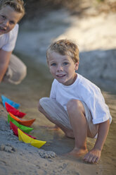 Two boys playing with paper boats on the beach - ZEF007938