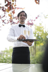 Waiter outdoors serving champagne - ZEF007950