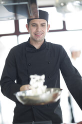Smiling chef cooking in kitchen - ZEF007956