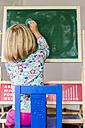 Little girl writing on blackboard - JFEF000464