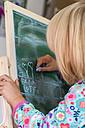 Little girl drawing on blackboard - JFEF000466