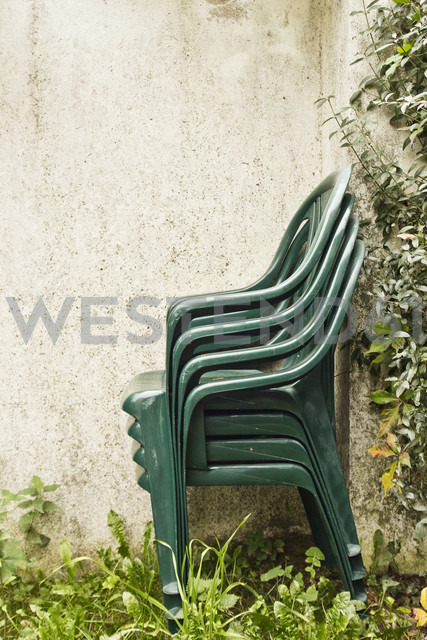 Stack of green garden chairs placed next to a wall - MELF000034
