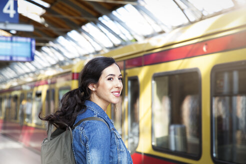 Germany, Berlin, young woman waiting in front of city train - FKF000741