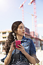 Germany, Berlin, portrait of young female tourist orientating with her smartphone - FKF000712