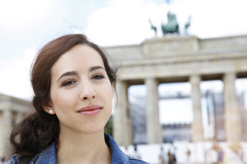 Germany, Berlin, portrait of young female tourist on city trip in front of Brandenburg Gate - FKF000714