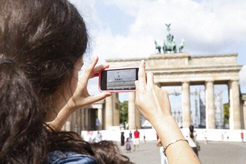 Germany, Berlin, female tourist photographing Brandenburg Gate with smartphone - FKF000720
