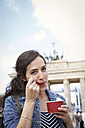 Germany, Berlin, portrait of young female tourist eating ice cream near Brandenburg Gate - FKF000723