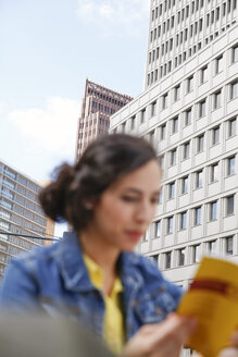 Germany, Berlin, young woman reading guidebook in front of facades at Potsdam Square - FKF000729