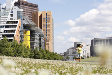 Germany, Berlin, happy young woman running on a meadow near Potsdam Square - FKF000735
