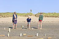 Mother and three children playing Kubb on the beach - LAF001194