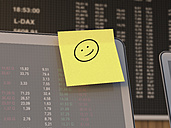 Germany, Stock exchange trading, Laptop with memo and smiley in the foreground - UWF000203