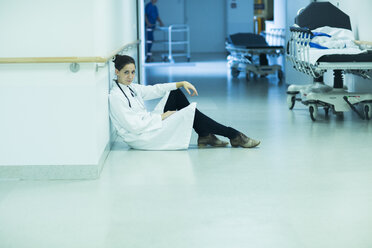 Overstressed young doctor sitting on hospital corridor - SGF000910
