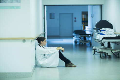 Overstressed young doctor sitting on hospital corridor - SGF000911