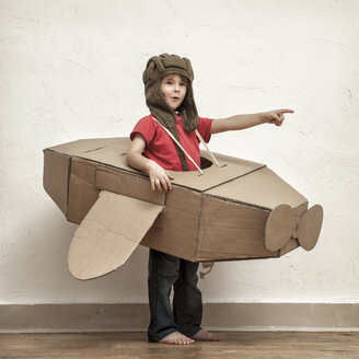 Little boy with pilot hat and cardboard box aeroplane showing at something - MMFF000405