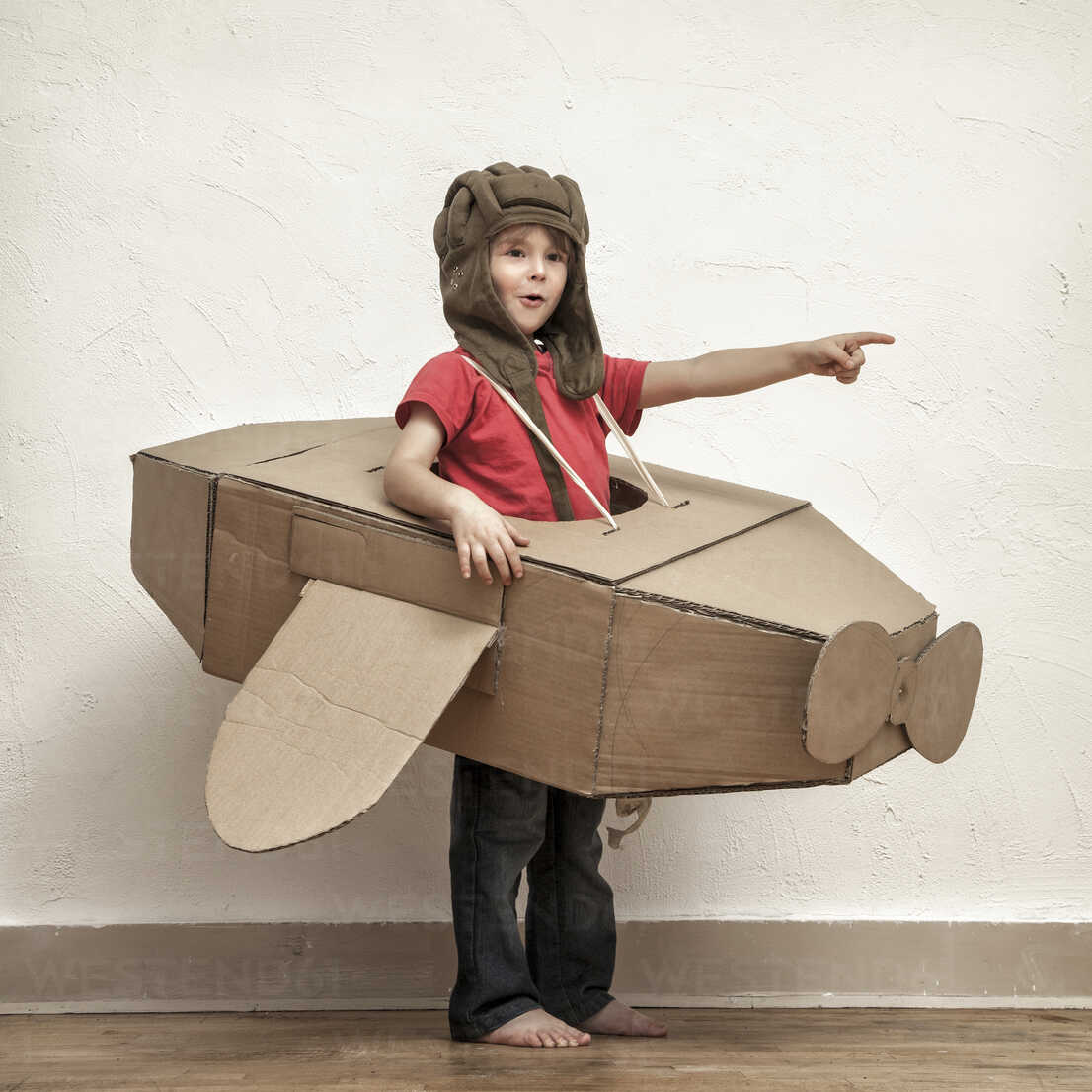 Little boy with pilot hat and cardboard box aeroplane showing at something - MMFF000405 - Mimafoto/Westend61