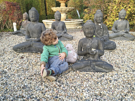 Boy looking at and talking with Buddha statues - AF000139