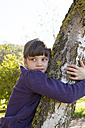 Portrait of girl hugging birch tree - LVF002148
